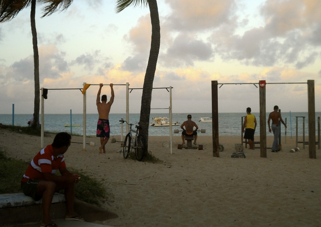 Guys working out on the beach.