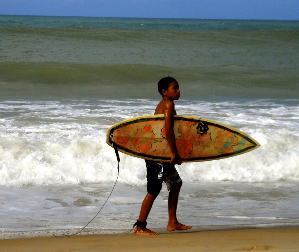 Brazilian boy with his surfboard.