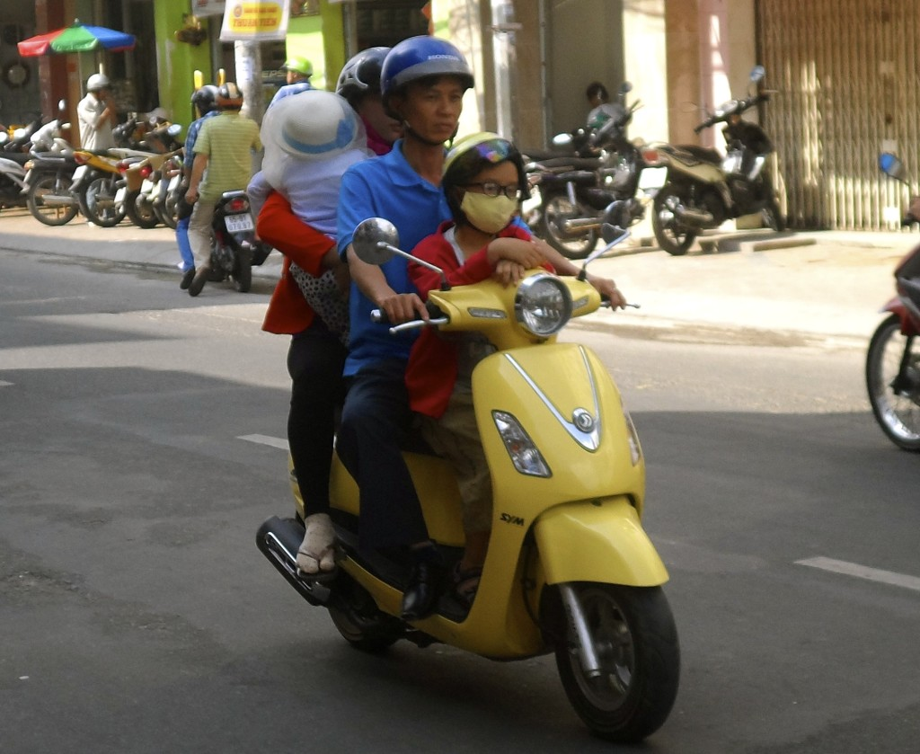 Family of 4 on a scooter in Vietnam.