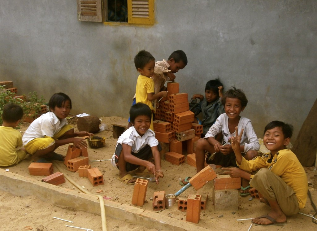 Happy cambodian school children and their simple toys.