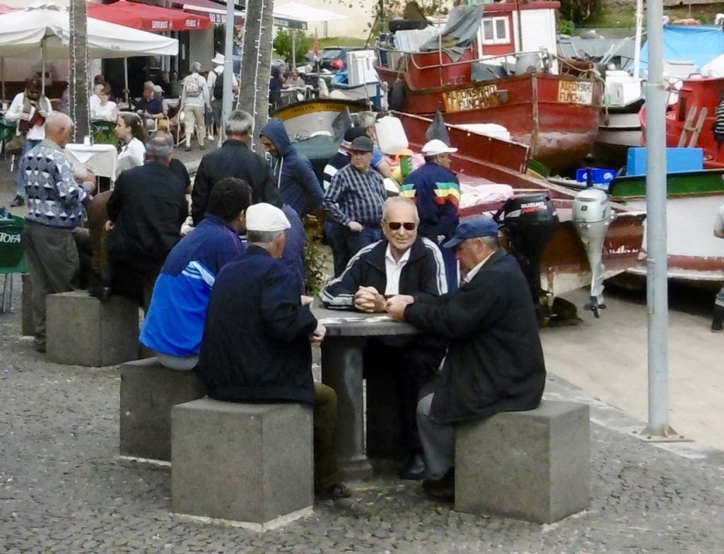 Old men playing cards by the harbour in Camara de Lobos.