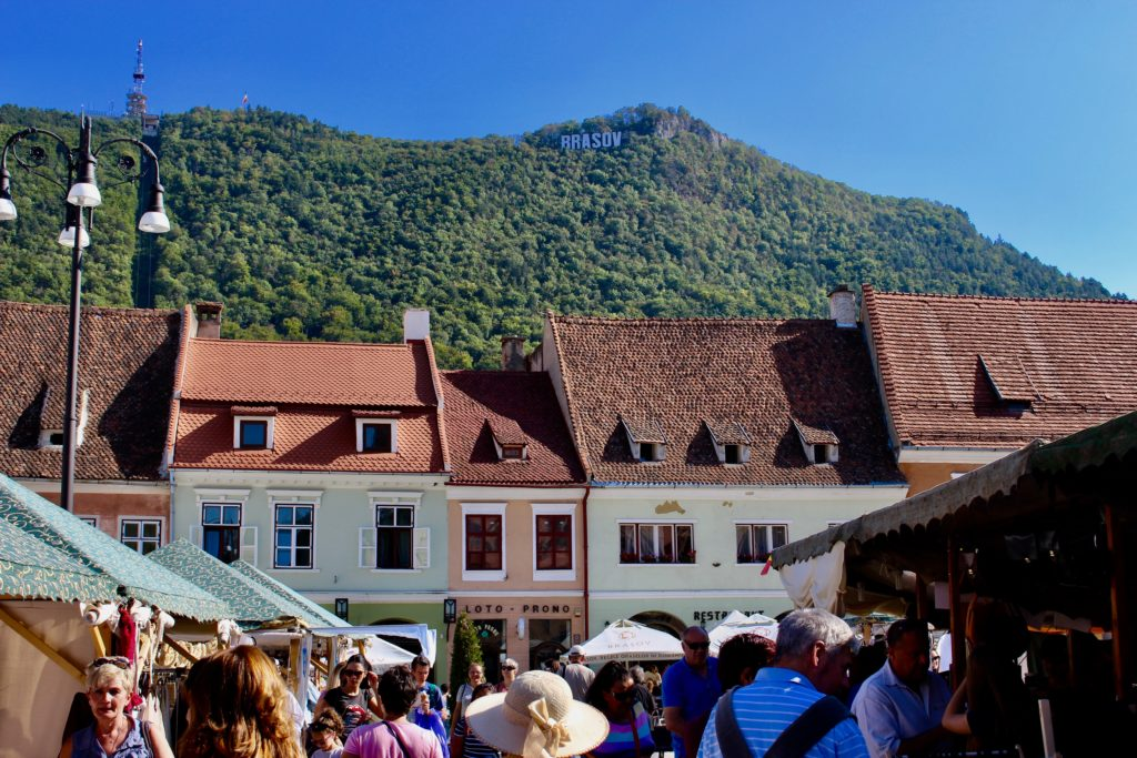 Brasov is a lively town surrounded by mountains.